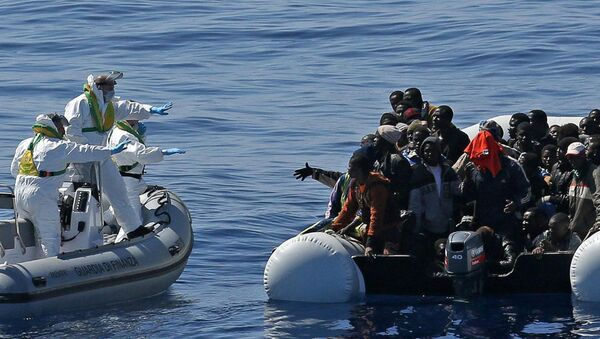 Italian Financial Police rescue unit approaches an inflatable dinghy crowded with migrants off the Libyan coast, in the Mediterranean Sea, Wednesday, April 22, 2015 - Sputnik France