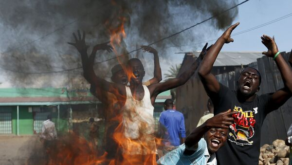 Protesters, who are against President Pierre Nkurunziza's decision to run for a third term, gesture in front of a burning barricade in Bujumbura, Burundi May 14, 2015. - Sputnik France