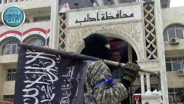 Un combattant du Front al-Nosra en Syrie tient le drapeau de ce groupe terroriste - Sputnik France