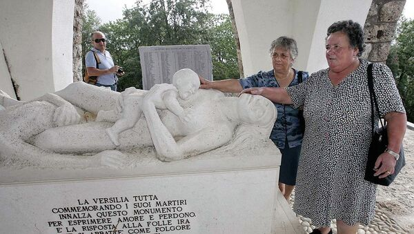 Lilia Pardini, right, and her sister Licia touch a sculpture depicting their mother and sister who were killed together with 560 people in 1944 by Nazi SS troops, at the 60th anniversary commemoration ceremony of the slaughter in Sant'Anna di Stazzema, Italy, Thursday, Aug. 12, 2004. - Sputnik France