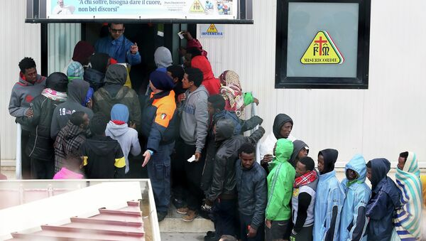 Migrants stand in front of the infirmary at the immigration centre on the southern Italian island of Lampedusa - Sputnik France