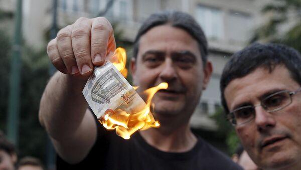 Мужчина сжигает евро-банкноту во время акции протеста против ЕС в Греции - Sputnik France