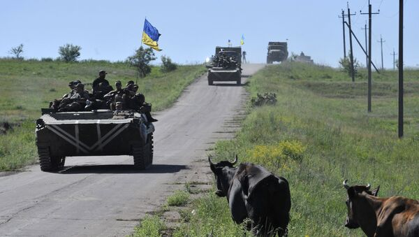 Members of the Ukrainian armed forces drive armoured vehicles and trucks as cows gather on the roadside near the village of Vidrodzhennya outside Artemivsk, Donetsk region, Ukraine, June 9, 2015. - Sputnik France