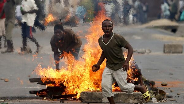 A protester runs in front of a burning barricade during a protest against Burundi President Pierre Nkurunziza and his bid for a third term in Bujumbura, Burundi, May 21, 2015 - Sputnik France