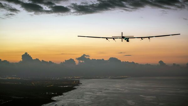 In this photo provided by Jean Revillard, Solar Impulse 2, a plane powered by the sun's rays and piloted by Andre Borschberg, approaches Kalaeloa Airport near Honolulu, Friday, July 3, 2015 - Sputnik France