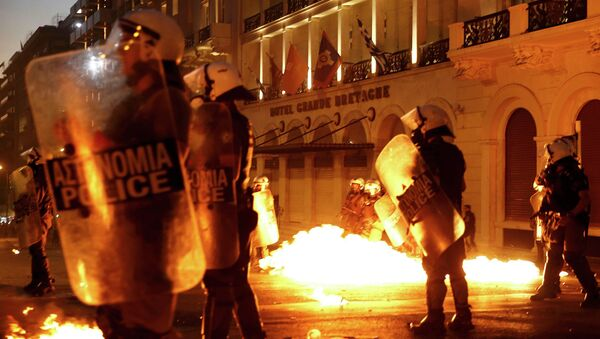 Riot police stand amongst the flames from exploded petrol bombs thrown by a small group of anti-austerity demonstrators in front of parliament in Athens, Greece July 15, 2015 - Sputnik France