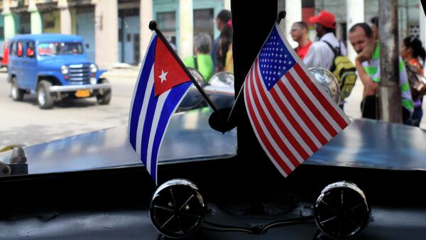 Miniature flags representing Cuba and the United States are displayed on the dash of an American classic car in Havana, Cuba. - Sputnik France