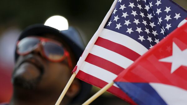 A man with small U.S. and Cuba flags stands on the sidewalk in the hours before officials raise the flag at the Cuban Embassy in Washington July 20, 2015. - Sputnik France