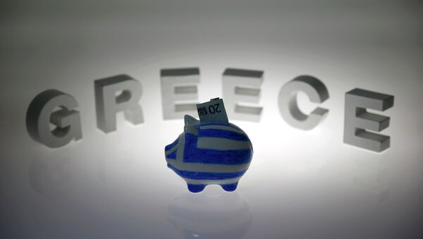 A piggybank painted in the colours of the Greek flag with a 20 euro banknote in it's slot, stands in front of letters spelling the word 'GREECE' in this picture illustration taken in Berlin, Germany June 30, 2015 - Sputnik France