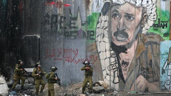 Israeli troops advance past a mural of the late Palestinian leader Yasser Arafat during clashes after a funeral in the Qalandia refugee camp near the West Bank city of Ramallah, Friday, Nov. 29, 2013. Palestinians buried Mahmud Awad, 22, who died of his injuries after he was shot during clashes with Israeli troops in March. - Sputnik France