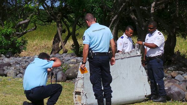 French gendarmes and police inspect a large piece of plane debris which was found on the beach in Saint-Andre, on the French Indian Ocean island of La Reunion, July 29, 2015. - Sputnik France