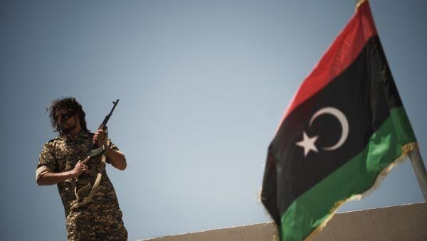 Un membre des forces de sécurité libyennes se tient sur un toit alors que le ministre libyen de la justice par intérim, Ali Hamiada, visite la nouvelle prison d'Al-Hadba et le tribunal spécial le 26 mai 2012 à Tripoli. La prison, qui peut accueillir 100 prisonniers politiques de haut rang, accueillera les procès des personnalités pro-mamer Kadhafi - Sputnik France