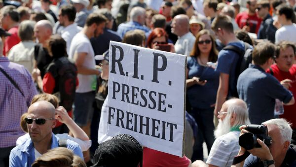 A demonstrator holds up a placard which reads Rest in Peace freedom of press! during a rally to protest against a criminal complaint by the domestic intelligence agency, the Office for the Protection of the Constitution (BfV), over articles about it that appeared on the Netzpolitik.org blog, in Berlin, Germany, August 1, 2015 - Sputnik France