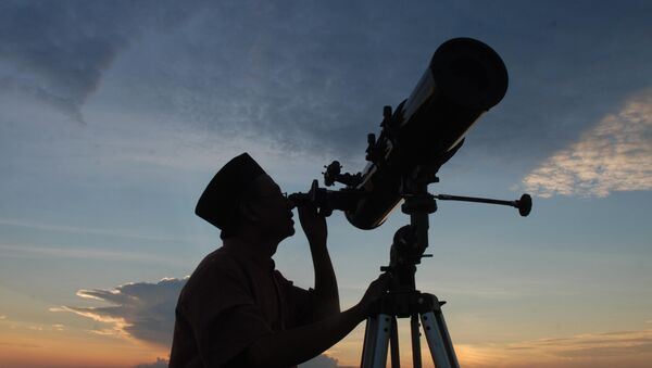 In this photograph taken on August 10, 2010 an official from the State Islamic University (STAIN), uses a telescope to observe the moon after sunset from the coast of Madura in East Java province of Indonesia on the eve of Ramadan - Sputnik France