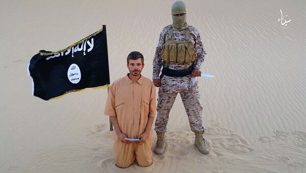 This image made from a militant video posted on a social media website on Wednesday, Aug. 5, 2015, which has been verified and is consistent with other AP reporting, purports to show a militant standing next to another man who identifies himself as 30-year-old Tomislav Salopek, kneeling down as he reads a message at an unknown location - Sputnik France