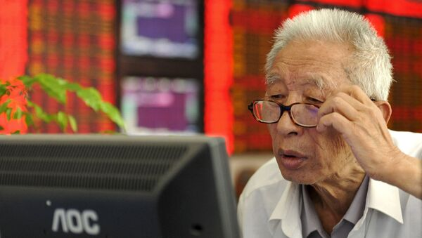 An investor adjusts his glasses as he looks at a computer screen in front of an electronic board showing stock information at a brokerage house in Fuyang, Anhui province, China, July 9, 2015. - Sputnik France