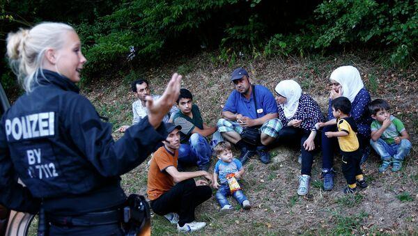 Une policière allemande se tient à côté de deux familles de réfugiés syriens près de Passau - Sputnik France