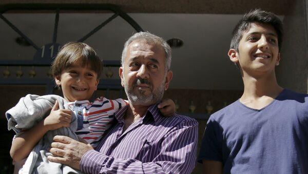 Osama Abdul Mohsen avec s fils dans les mains, le 16 septembre - Sputnik France