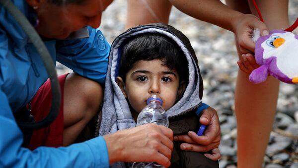 Une volontaire donne à boire à un petit réfugié syrien - Sputnik France