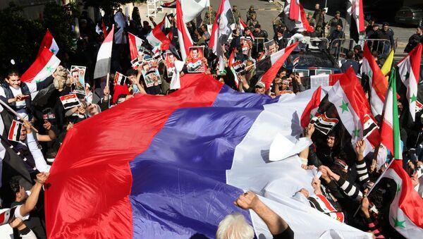 Pro-Syrian regime protesters wave a large Russian flag during a demonstration - Sputnik France