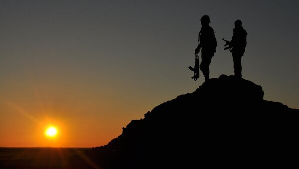 People's Protection Units (YPG) fighters stand on top of a hill at sunset on February 26, 2015, after they retook parts of the town of Tal Hamis, southeast of the city of Qameshli, after six days of clashes with Islamic State (IS) group jihadists in Syria's Hasakeh province. - Sputnik France