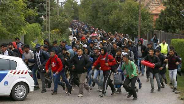 Migrants run as they follow a police vehicle on their way to the Austrian border in Nickelsdorf from Hegyeshalom, Hungary September 25, 2015. - Sputnik France