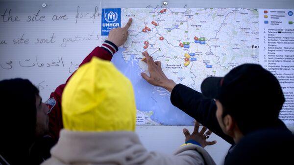Des migrants examinent une carte des Balkans de l'Ouest, Oct. 27, 2015. - Sputnik France
