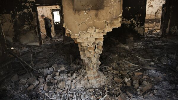 A man wearing a surgical mask walks, 14 October 2015, amongst the debris of the damaged and burnt-out MSF Trauma Centre in Kunduz, northern Afghanistan - Sputnik France
