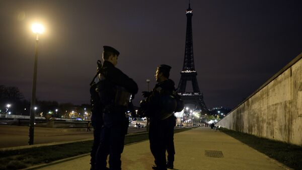 Police officers stand guard near the Eiffel Tower which has its lights turned off on November 14, 2015 following the deadly attacks in Paris. - Sputnik France