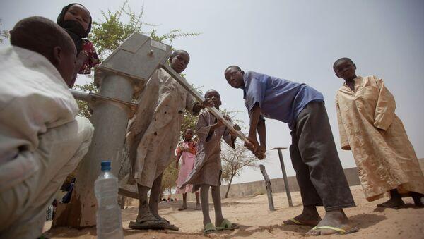 Des enfants pompent de l'eau pour boire dans un puits dans la cour d'un centre d'alimentation sans rendez-vous à Dibinindji, un village du désert dans la ceinture du Sahel au Tchad - Sputnik France