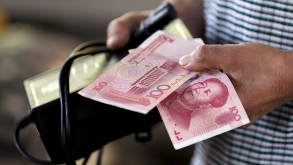 A customer holds a 100 Yuan note at a market in Beijing, August 12, 2015 - Sputnik France