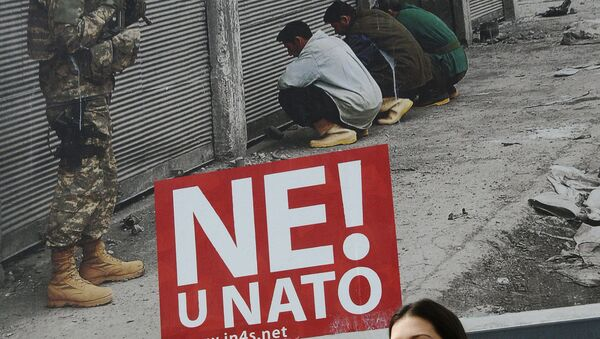 A Montenegrin woman walks past a billboard with the reading, No to NATO in Podgorica, on April 3, 2009 - Sputnik France