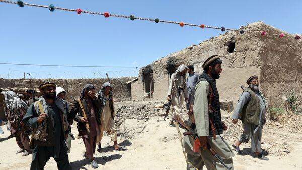 Sur cette photo de fichier du jeudi 21 mai 2015, des combattants d'une milice locale passent devant un bâtiment incendié par des combattants talibans dans le village de Talawka, dans la province de Kunduz, au nord de Kaboul, en Afghanistan. - Sputnik France