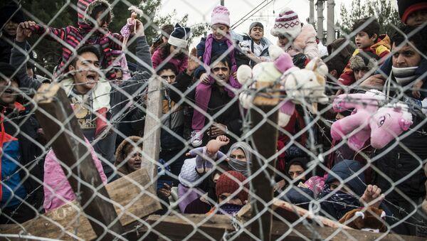 Des migrants protestent derrière une clôture contre les restrictions limitant le passage à la frontière gréco-macédonienne, près de Gevgelija, le 1er décembre 2015. Depuis la semaine dernière, la Macédoine limite le passage vers le nord de l'Europe aux seuls Syriens, Irakiens et Afghans qui sont considérés comme des réfugiés de guerre. Toutes les autres nationalités sont considérées comme des migrants économiques et priées de faire demi-tour. Le 29 novembre, la Macédoine a terminé la construction d'une clôture à sa frontière avec la Grèce, devenant ainsi le dernier pays d'Europe à construire une barrière frontalière visant à contrôler le flux de migrants. - Sputnik France