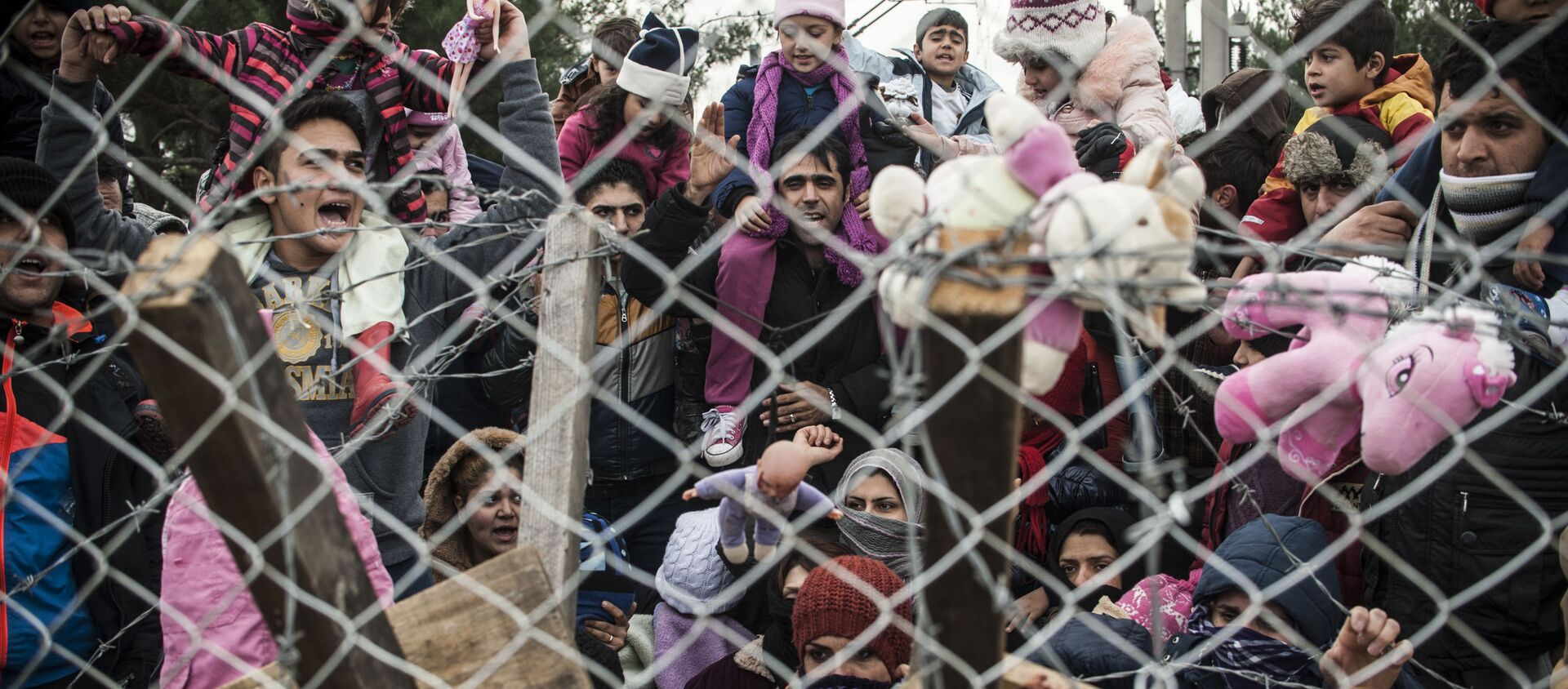 Des migrants protestent derrière une clôture contre les restrictions limitant le passage à la frontière gréco-macédonienne, près de Gevgelija, le 1er décembre 2015. Depuis la semaine dernière, la Macédoine limite le passage vers le nord de l'Europe aux seuls Syriens, Irakiens et Afghans qui sont considérés comme des réfugiés de guerre. Toutes les autres nationalités sont considérées comme des migrants économiques et priées de faire demi-tour. Le 29 novembre, la Macédoine a terminé la construction d'une clôture à sa frontière avec la Grèce, devenant ainsi le dernier pays d'Europe à construire une barrière frontalière visant à contrôler le flux de migrants. - Sputnik France, 1920, 20.08.2021