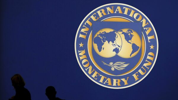 Les silhouttes des visiteurs sur le logo du Fonds monétaire international sur le site principal de la réunion annuelle du FMI et de la Banque mondiale à Tokyo Octobre 10, de 2012. - Sputnik France