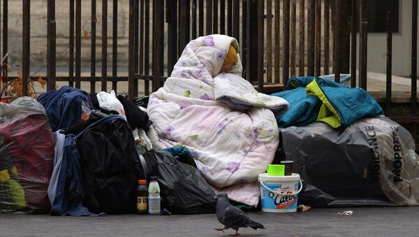 A homeless woman is wrapped in a blanket on the sidewalk of a Parisian street - Sputnik France