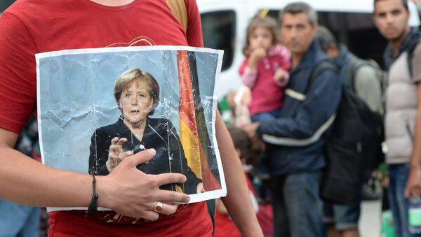 Un migrant tient le portrait d'Angela Merkel - Sputnik France
