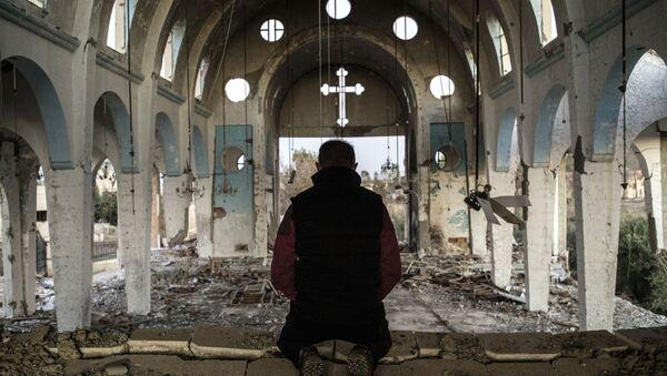 Un chrétien syrien prie dans l'église de Saint-Georges, détruite par l'EI (Daech) - Sputnik France