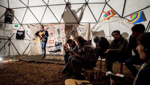 migrants écoutent un guitariste dans un théâtre improvisée, Calais - Sputnik France