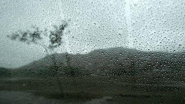 Un paysage est vu à travers une fenêtre humide de l'intérieur d'une voiture à Lima - Sputnik France