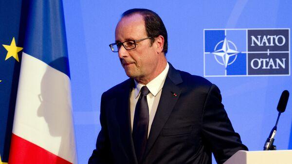 Une ombre du président François Hollande de la France est jeté sur un drapeau comme il laisse une conférence de presse sur la deuxième journée du sommet de l'OTAN 2014 au Celtic Manor Resort à Newport, au Pays de Galles du Sud, le 5 Septembre, 2014 - Sputnik France