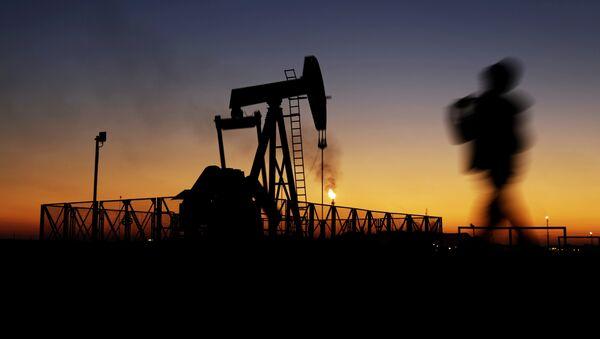 A boy walks by an oil pump at sunset Monday, Jan. 18, 2016, in the desert oil fields of Sakhir, Bahrain.  - Sputnik France