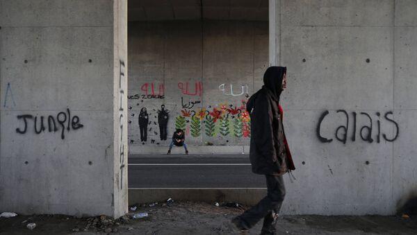 Les immigrants font leur chemin le long d'une route près de graffiti avec les mots Jungle, Calais à Calais, France, le 20 Octobre 2015. - Sputnik France