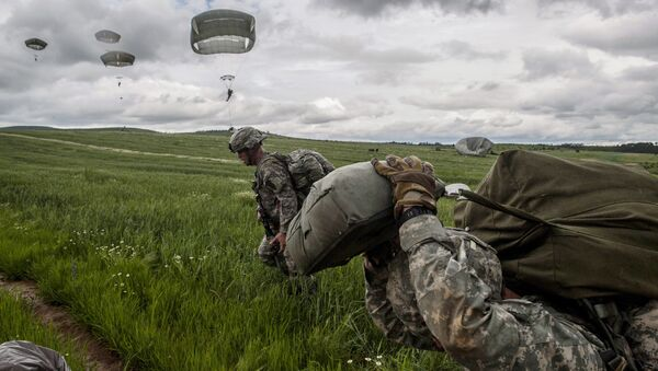 US para-troopers of the Army's 4th 25 Infantry Brigade Combat Team (Airborne), part of the NATO-led peacekeeping mission in Kosovo (KFOR) jump with parachute during a military drill near the village of Ramjan on May 27, 2015 - Sputnik France