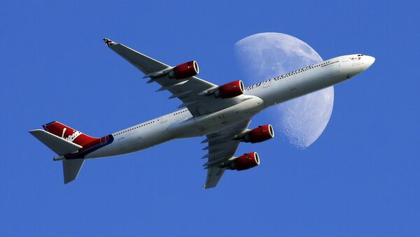 A Virgin Atlantic passenger plane crosses a waxing gibbous moon on its way to the Los Angeles International Airport, Sunday, Aug. 23, 2015, in Whittier, Calif - Sputnik France
