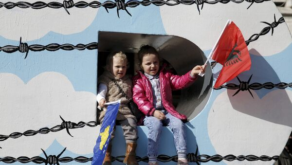 Children wave Albanian (R) and Kosovar flags on the Newborn monument during a celebration marking the eighth anniversary of Kosovo's declaration of independence from Serbia, in Pristina February 17, 2016. - Sputnik France