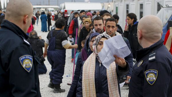 A migrant presents her document to Croatian police to board a train at a transit camp, near Gevgelija, Macedonia, February 18, 2016. - Sputnik France