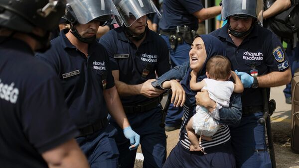 A migrant family is arrested by local police after their local train coming from Budapest and heading to the Austrian border has been stopped in Bicske, west of the Hungarian capital on September 3, 2015. - Sputnik France
