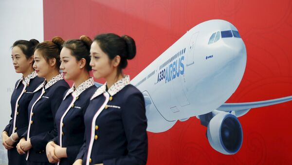 Staff members stand in front of a wall bearing the image of the Airbus A330 plane at a ground-breaking ceremony for the Airbus A330 completion and delivery center in Tianjin, China, March 2, 2016. - Sputnik France